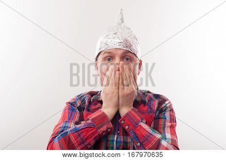 Young Man In A Cap Of Foil Covers Her Mouth In Fright. Afraid Of Radiation Or Aliens
