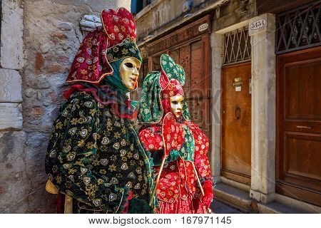 VENICE, ITALY - MARCH 04, 2011: Couple of participants in colorful dresses and masks on old street of Venice during traditional famous Carnival taking place each year on February in Venice.
