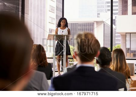 Young black woman at lectern presenting seminar to audience