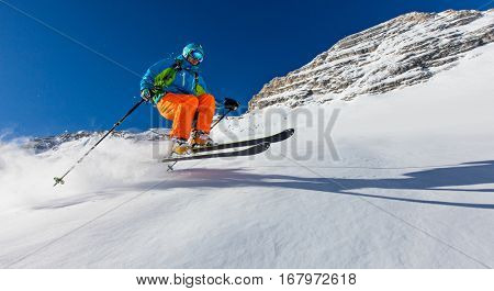 Freeride in fresh powder snow during sunny day.