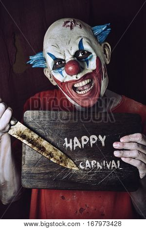 a scary evil clown pointing a big knife at a wore chopping board with the text happy carnival written in it