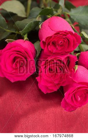 Closeup Of Red Roses Bouquet, On Red Fabric Background.