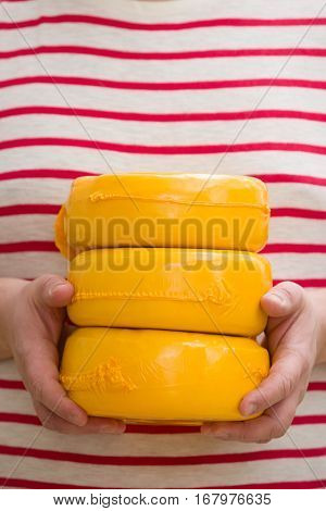 Three big organic cheese heads in yellow vacuum package in man's hands. Food concept