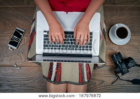 Woman view pictures from camera on her laptop. Top view, wooden background.