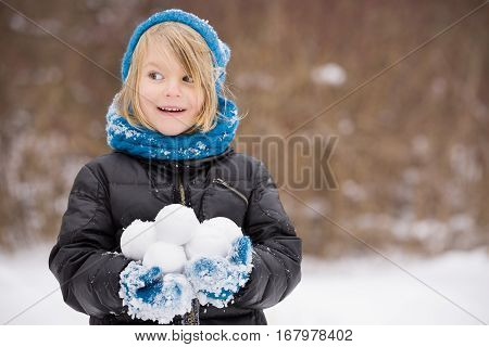 Portrait of adorable little kid boy with long blond hair playing with snowballs outdoors. Child with blue scarf and hat walking and having fun on a windy winter day.