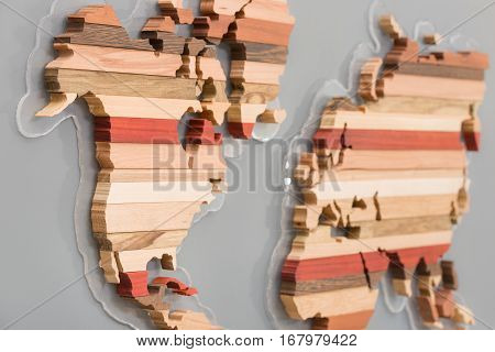 Handmade wooden map for home decoration. Art and abstract. Different types of wood in shape or continents on light grey background.