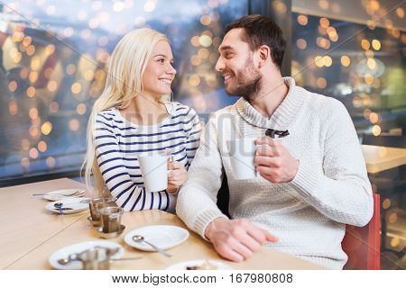 people, leisure and communication concept - happy couple meeting and drinking tea or coffee at cafe over holidays lights