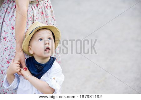 Portrait of a cute toddler boy on straw hat holding his mother's hand and looking at the sky. Adorable child with his mom walking in the park. Together. Childhood and lifestyle concept