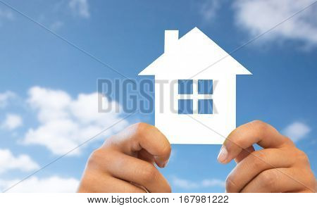 people, home, real estate and mortgage concept - close up of hands holding paper house
