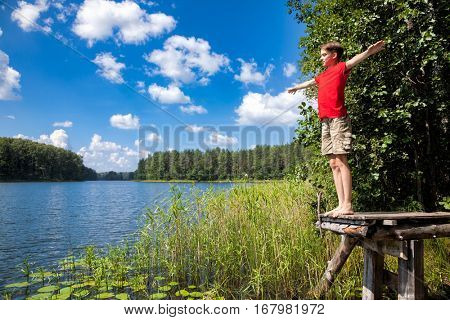 Teen boy spread out his hands sanding on a wooden pier in a summer forest