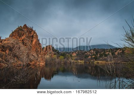 Landscape of red rock formations reflected in a lake as clouds pass by.
