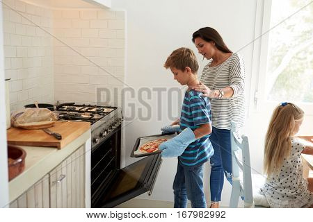 Mother And Children Baking Homemade Pizza In Oven