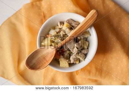 hand carved wooden spoon and a ragout on yellow background
