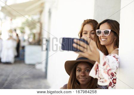 Three female friends taking a selfie in the street, Ibiza