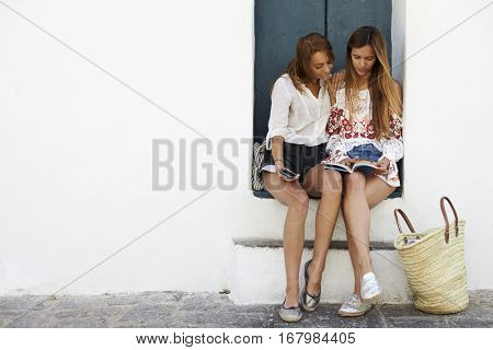 Female friends sitting in doorway reading a guidebook, Ibiza