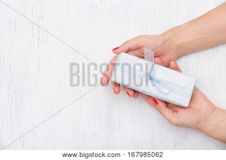 Top view on hands holding gift box with ribbon on white wooden background. Present for Christmas birthday or any celebration. Giving gift. Holidays and Christmas concept.