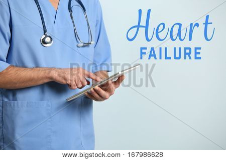 Cardiology and health care concept. Doctor working with tablet on color background