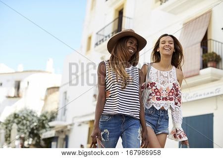 Two female friends on holiday walking, Ibiza, low angle view