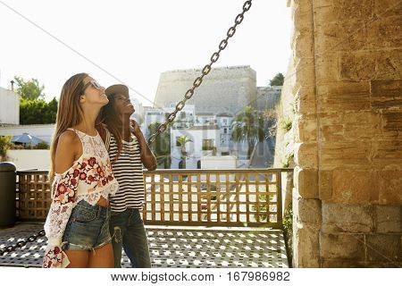 Two female friends on vacation admiring a building, Ibiza