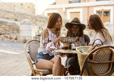 Female friends on holiday reading a guidebook outside a cafe