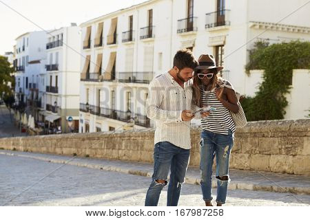 Young couple reading a guidebook in the street, Ibiza, Spain