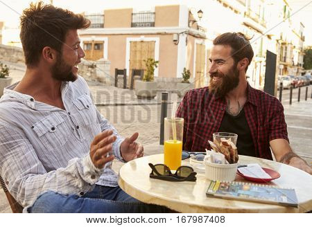 Two male friends taking at a table outside a cafe in Ibiza