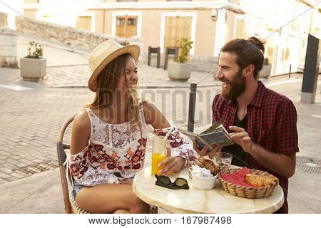 Laughing couple reading a guidebook outside a cafe in Ibiza