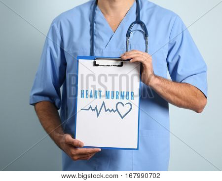 Cardiology and health care concept. Doctor's hands holding clipboard with text HEART MURMUR