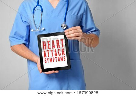 Cardiology and health care concept. Doctor's hands holding tablet with text HEART ATTACK SYMPTOMS