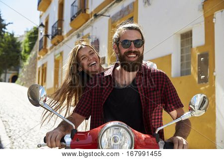 Couple sitting on a motor scooter laughing, Ibiza, Spain