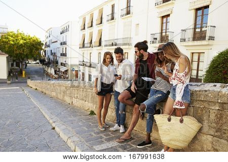 Friends on vacation in Ibiza looking at guidebook and phone