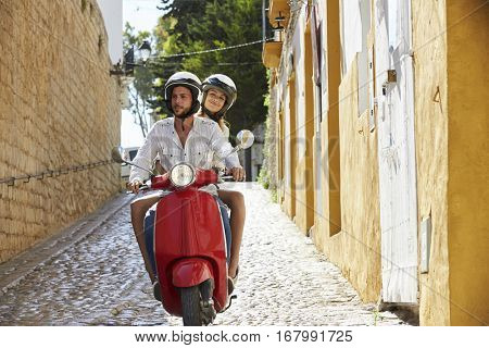 Couple riding motor scooter in old Ibiza street, front view