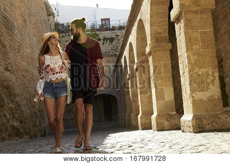 Couple sightseeing in Ibiza, looking at each other