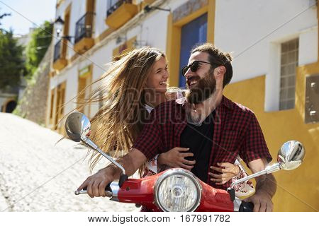 Couple sitting on motor scooter looking at each other, Ibiza