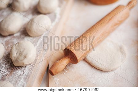 wooden rolling-pin and homemade dough ready for cooking pies
