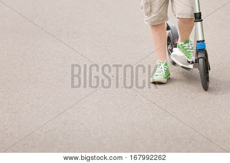 Closeup of kid's feet on scooter. Boy riding scooter in the park on sunny summer day. lifestyle concept