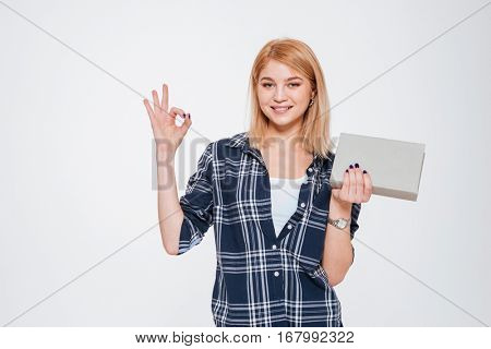 Picture of positive young woman holding book isolated on a white background make okay gesture.