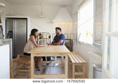 Adult couple talk and drink wine in the kitchen, full length