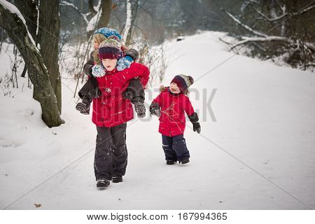 Children having fun while walking in a winter forest. Cute kid boy carrying his friend and an adorable little toddler running near by.Smiling children outdoors.