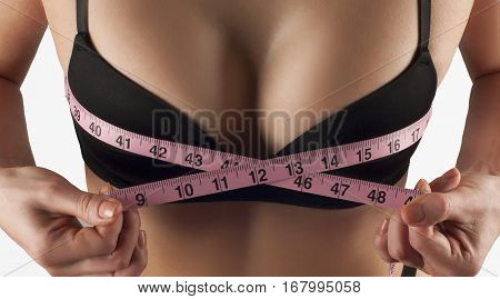 Closeup of young woman measures her breast with a measuring tape