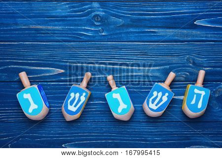 Dreidels for Hanukkah on blue wooden table
