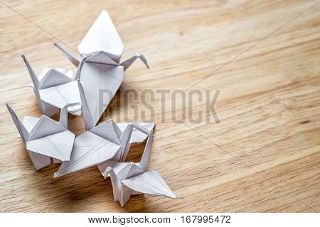 group of origami cranes made from white paper on a wooden table with copy space