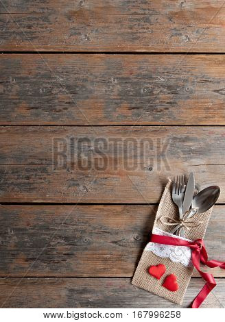 Romantic meal menu background, fork and knife inside a pouch with red ribbon