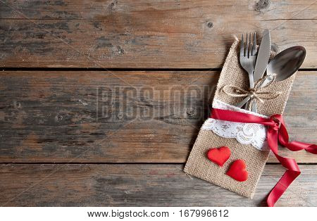 Cutlery set inside pouch with two red hearts and silk ribbon over a wooden background