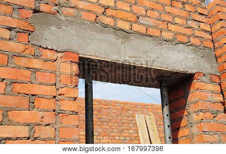 Building house construction. Window door concrete lintel with iron bar on brick unfinished house construction.