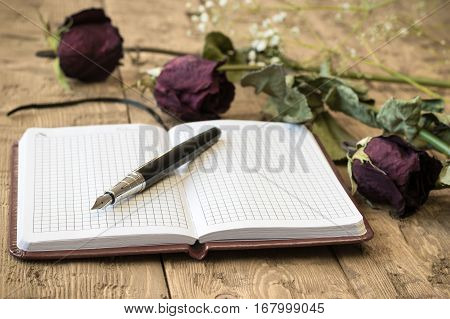Wilted roses with a notebook and fountain pen on a rustic table. Concept of holiday memories.