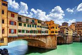 Side view of medieval stone bridge Ponte Vecchio over the Arno River in Florence Tuscany Italy. View from the Lungarno degli Archibusieri. Florence is a popular tourist destination of Europe. poster