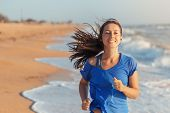 Running woman. Female runner jogging during outdoor workout on beach listening to music in earphones. Fitness woman running by the beach at sunrise. Healthy active lifestyle girl exercising outdoors poster