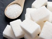 background of sugar cubes and sugar in spoon. White sugar on black background. Sugar cubes and granulated in wooden spoon poster