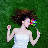 Portrait of a young redhead woman with pinwheel lying down on green spring grass above point of view poster